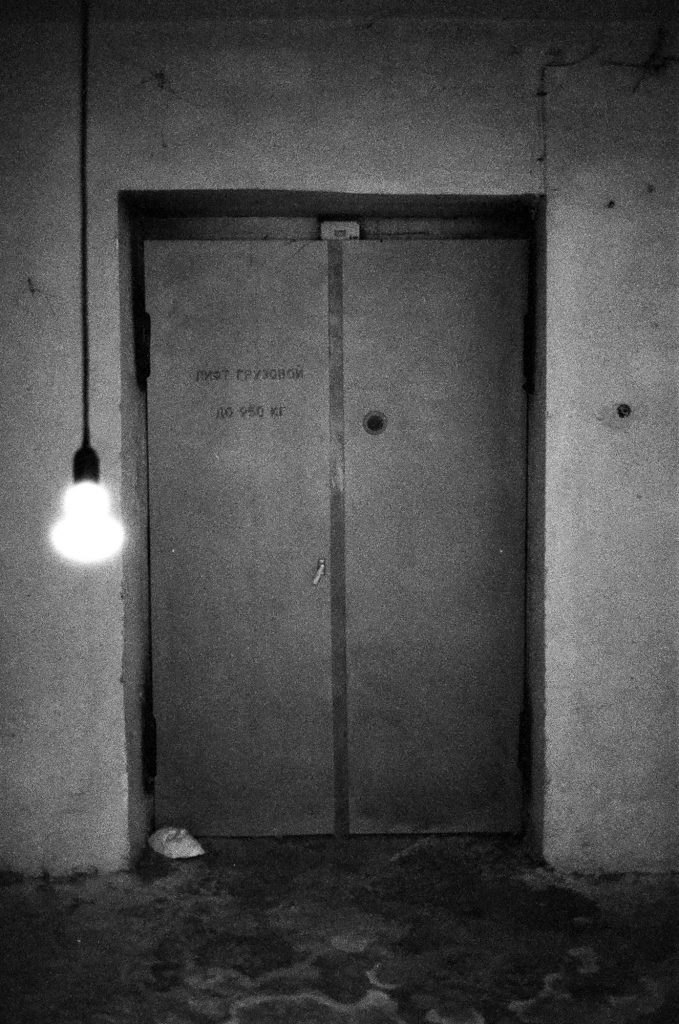 clack and white photo of doorway with hanging light bulb