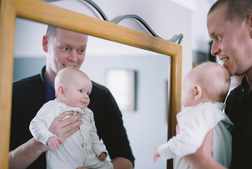 Man holding baby in mirror photographed with Contax T2