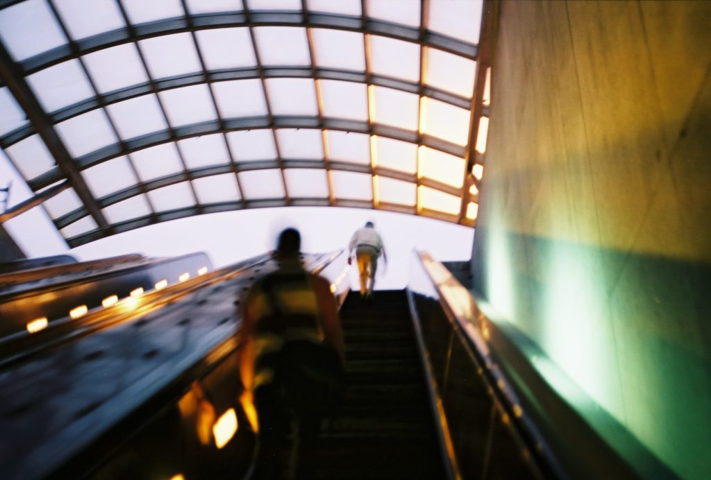 Image of commuters on an escalator upwards.