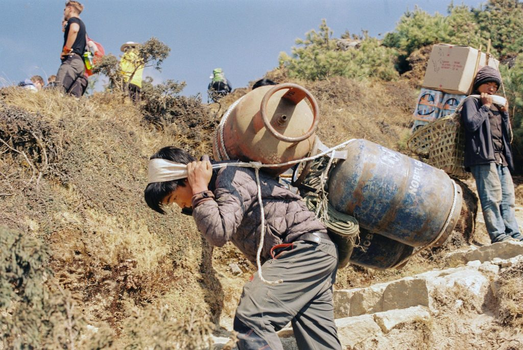 Boy carries 3 gas canisters up a mountain