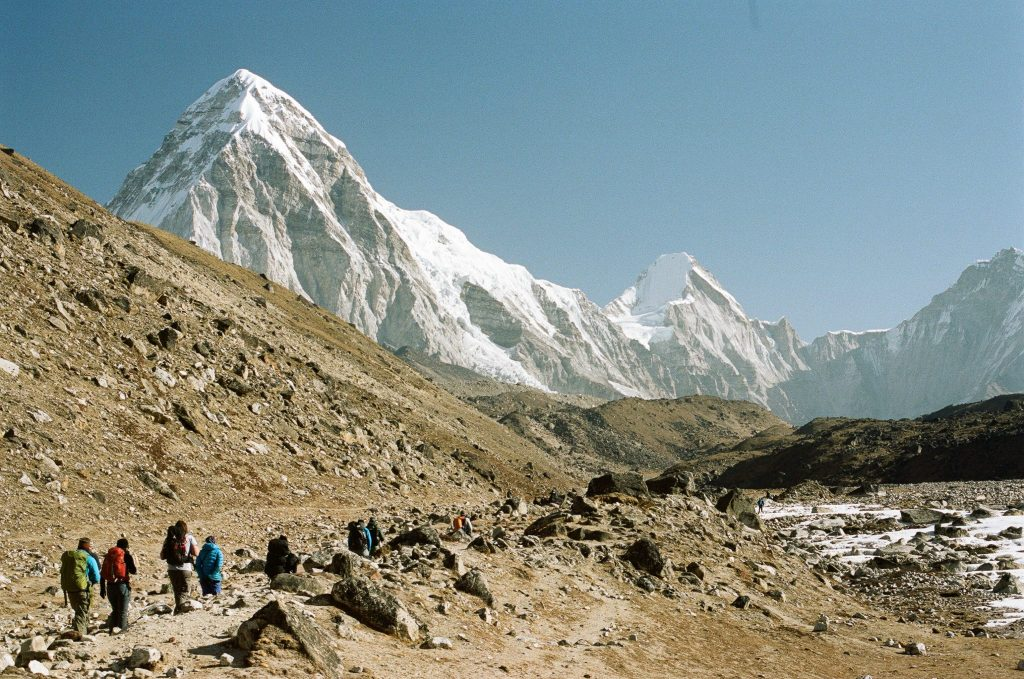 View of mountains with people walking up a valley