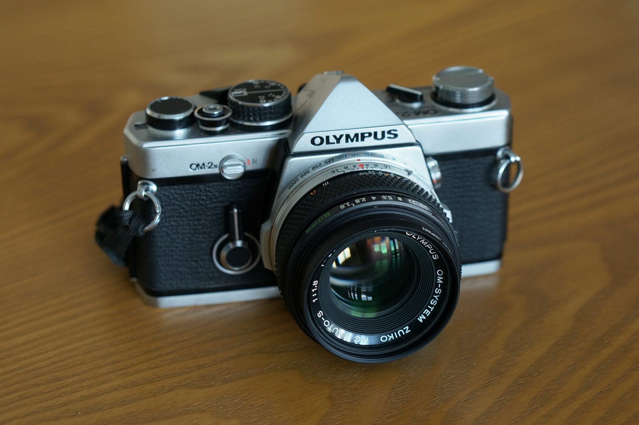 Picture of an Olympus OM-2n on a table with 50mm f/1.8 lens