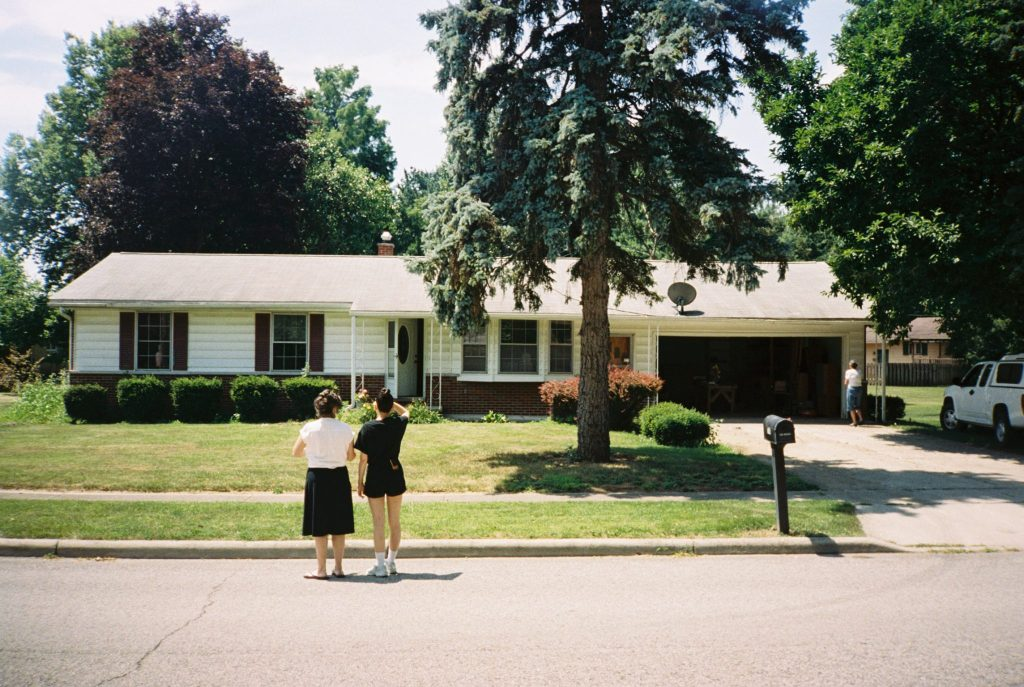 Minolta AF 35R QD photo of two women standing in street in front of house