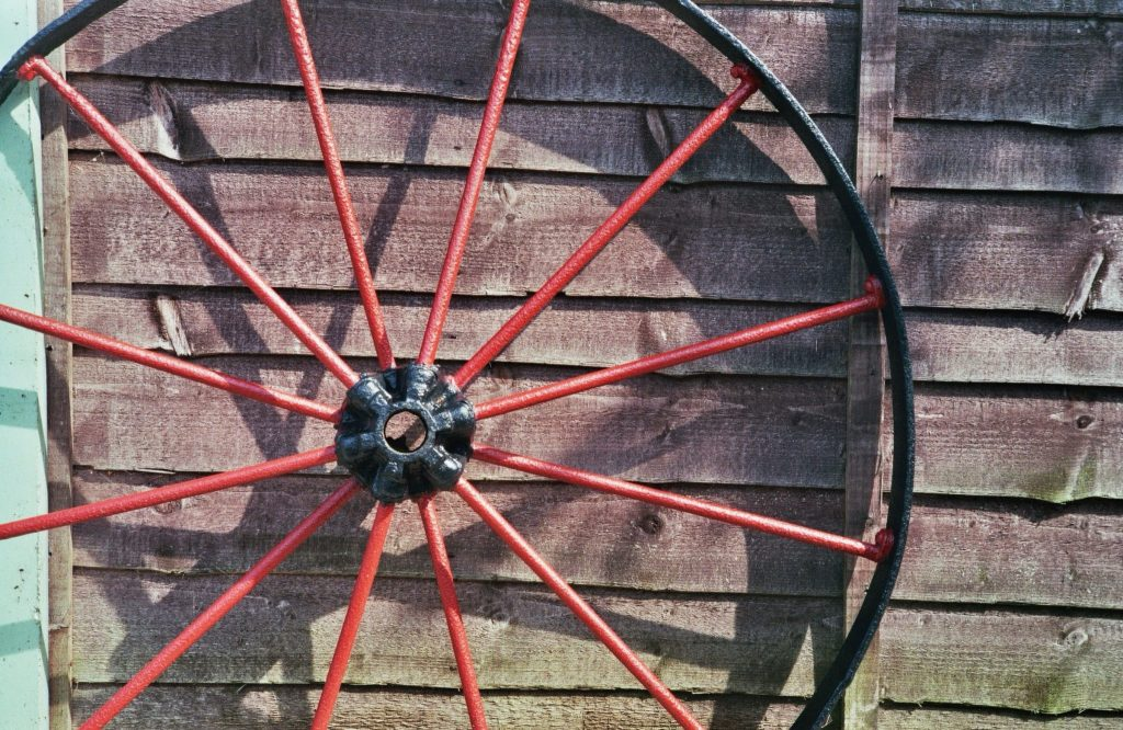 Red Waggon wheel in front of fence