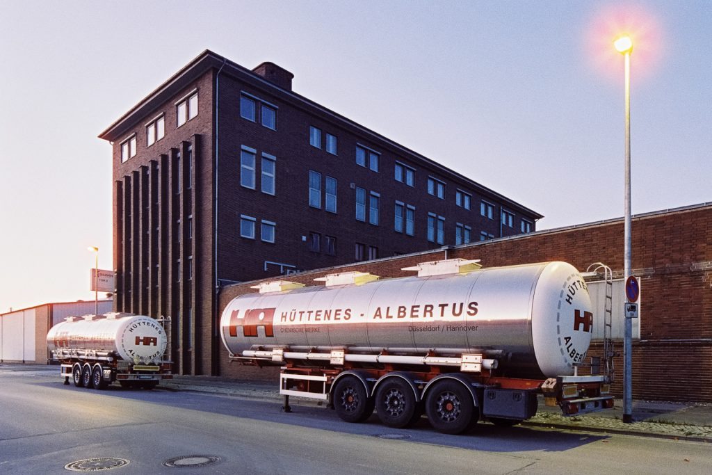 dark brick building with silver tank cars in the foreground, shot at dusk on CineStill film