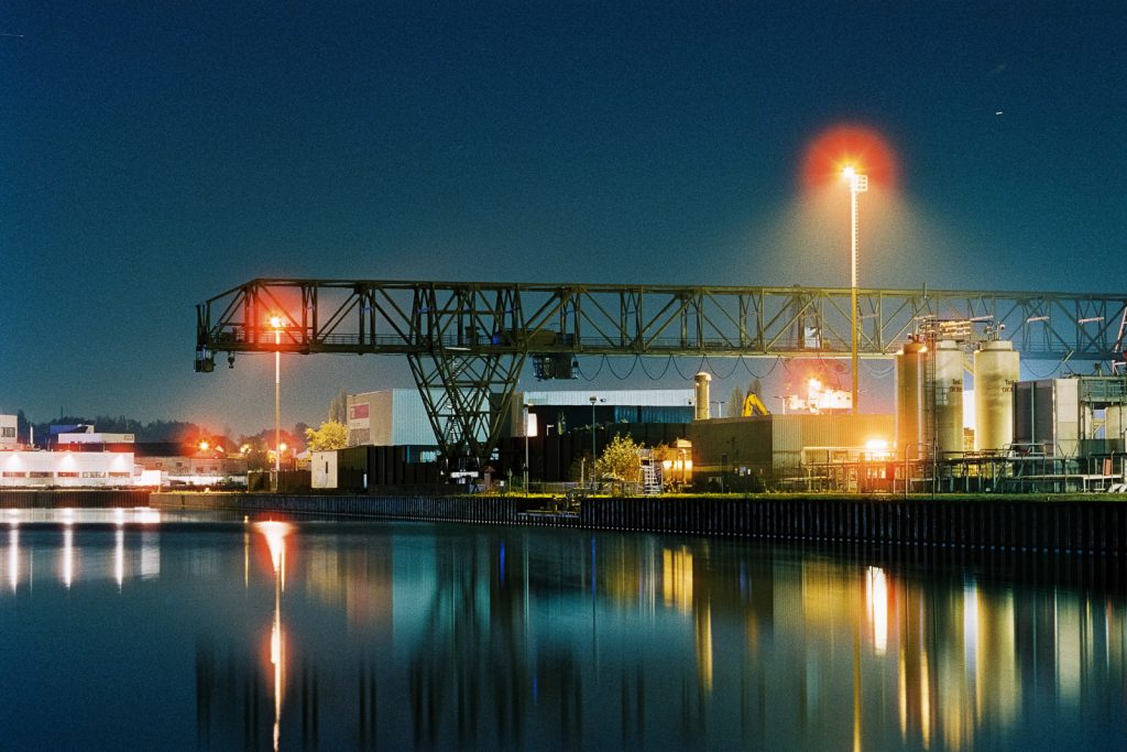 inland harbor with loading cranes shot at night on CineStill film