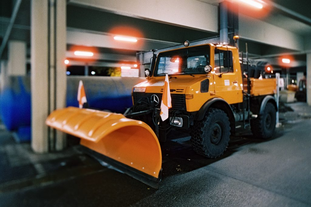 Orange snowplow (Mercedes Unimog) shot at night on CineStill film