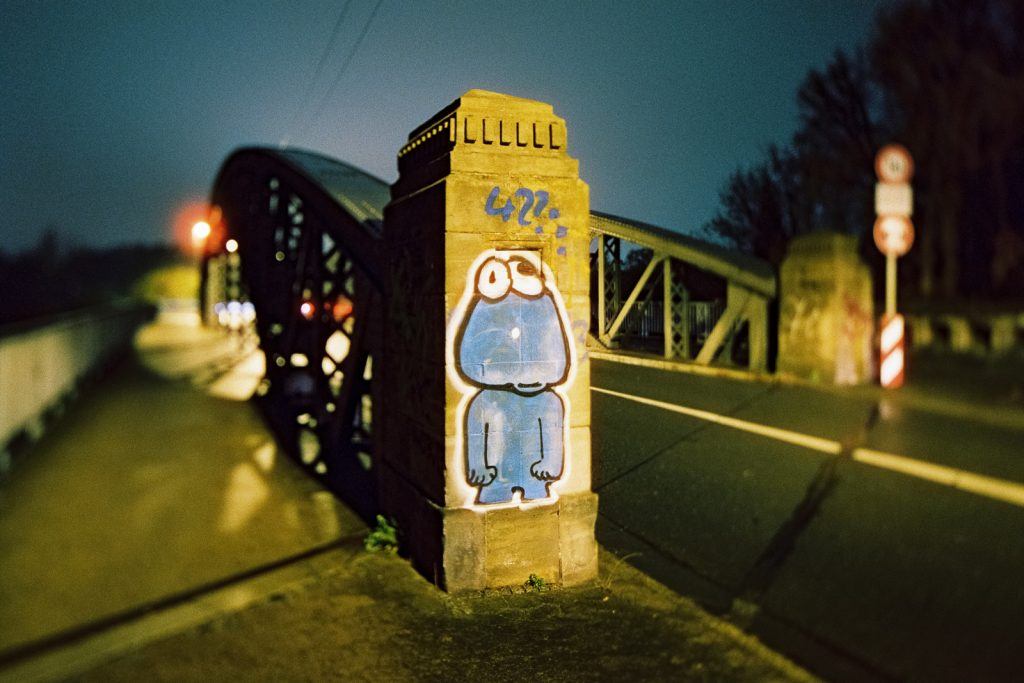 Graffiti on a bridge pylon shot at night on CineStill film