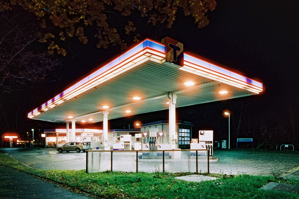 blue and red decorated filling station shot at night on CineStill film