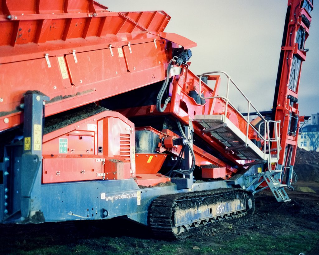 close-up of red construction machine shot at night on CineStill film