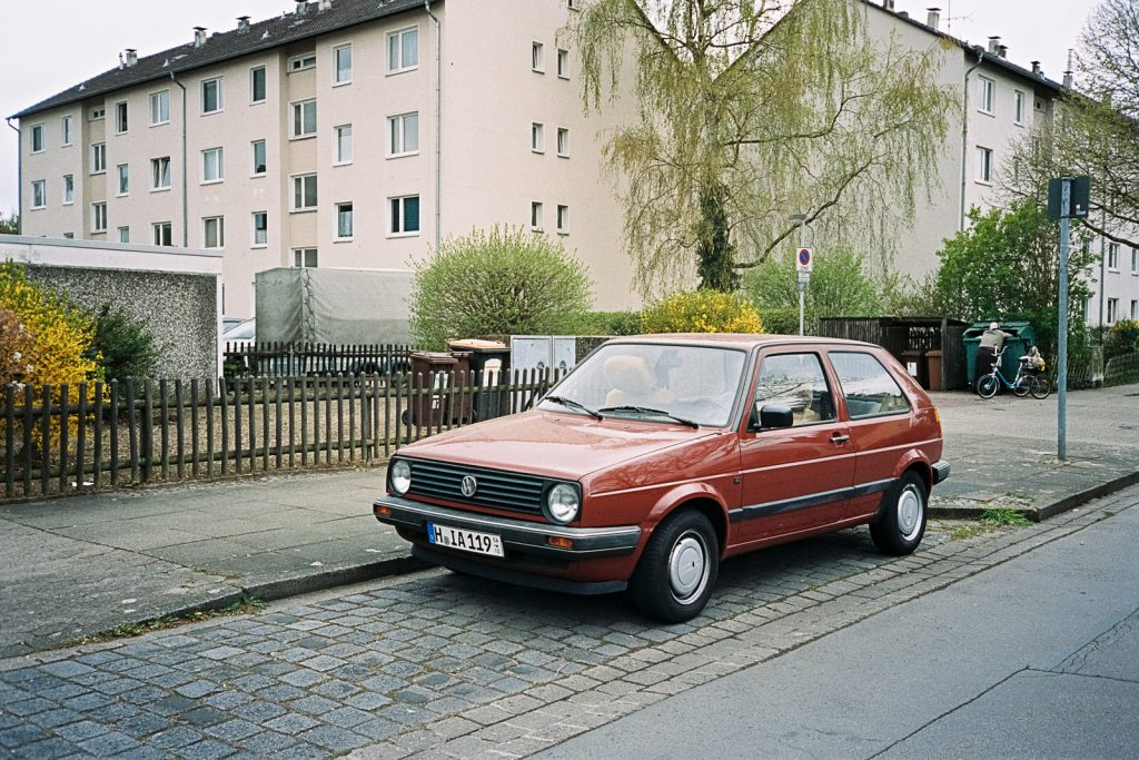 Volkswagen Golf Mk. II parking in front typical German houses from the 1960's, captured with a point-and-shoot camera