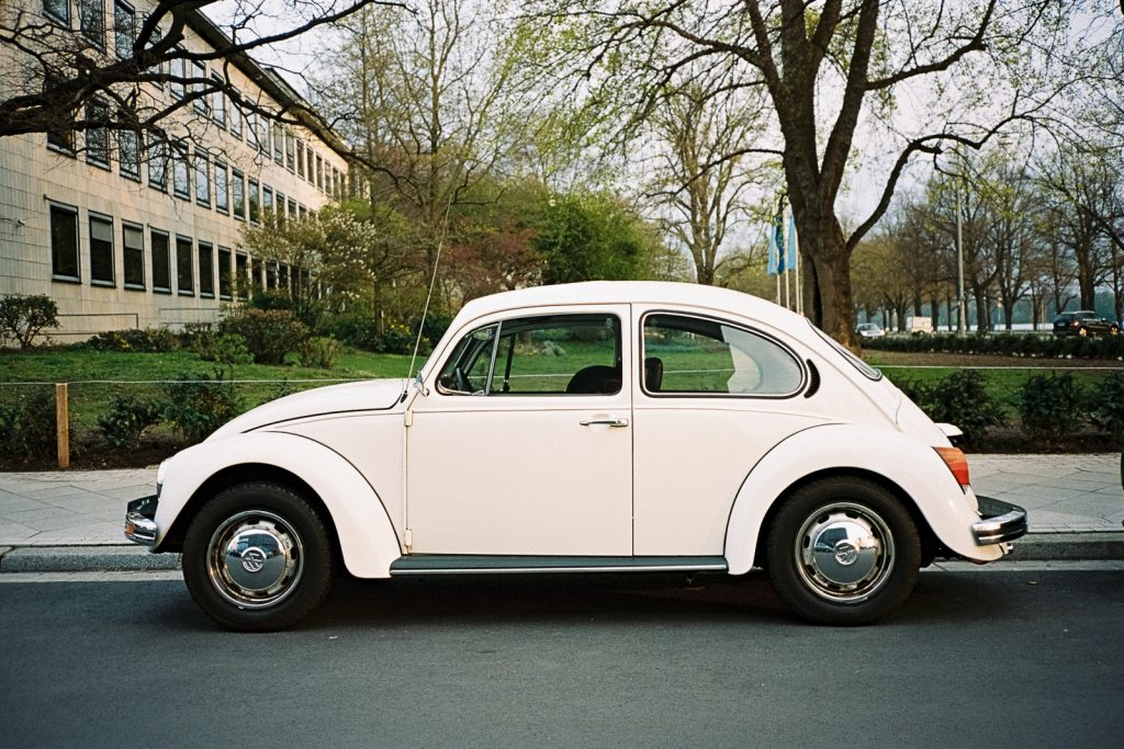 A white Volkswagen Beetle parked at the side of a road, captured with a point-and-shoot camera.