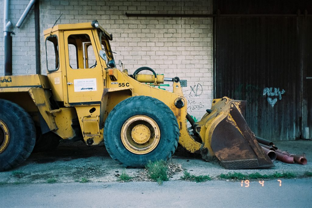 Wreck of a yellow loader standing in front of a wall