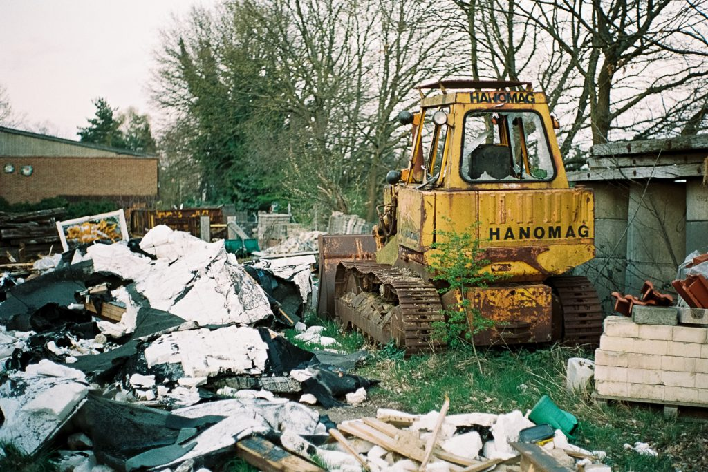 Wreck of a yellow bulldozers standing in a field of debris.