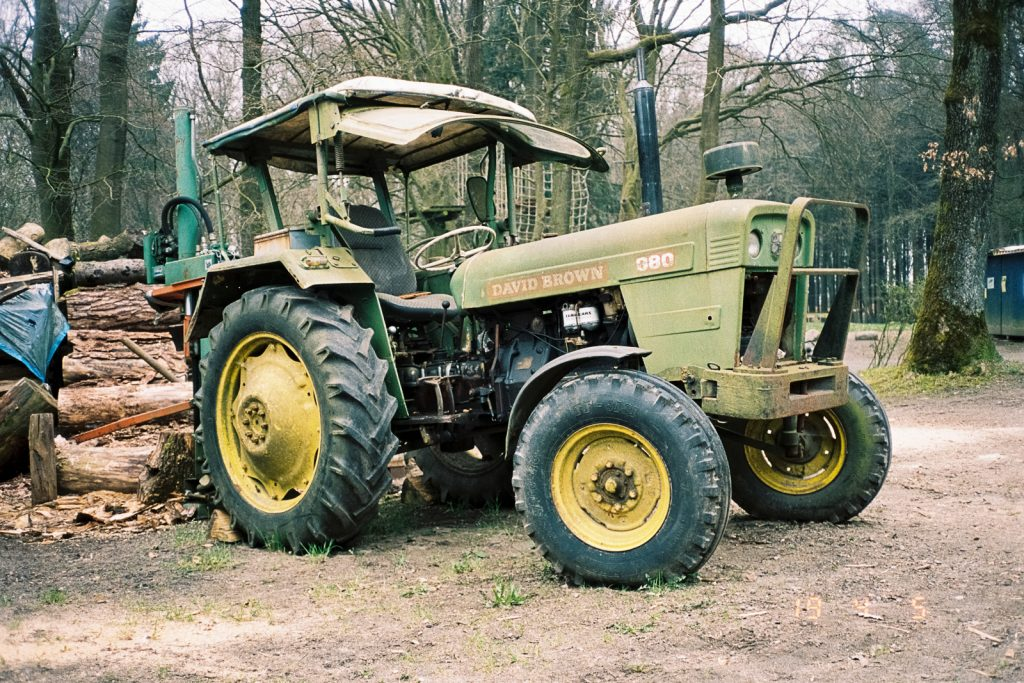A green old tractor with yellow wheels.