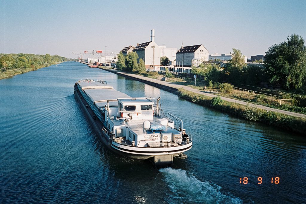 An inland vessel underway on the Mittelland Canal, captured with a Nikon L35 AD2 point-and-shoot camera.