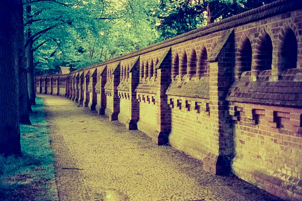 brick wall surrounding the Engesohde cemetery in Hannover, shot on CineStill 800t film with an orange filter