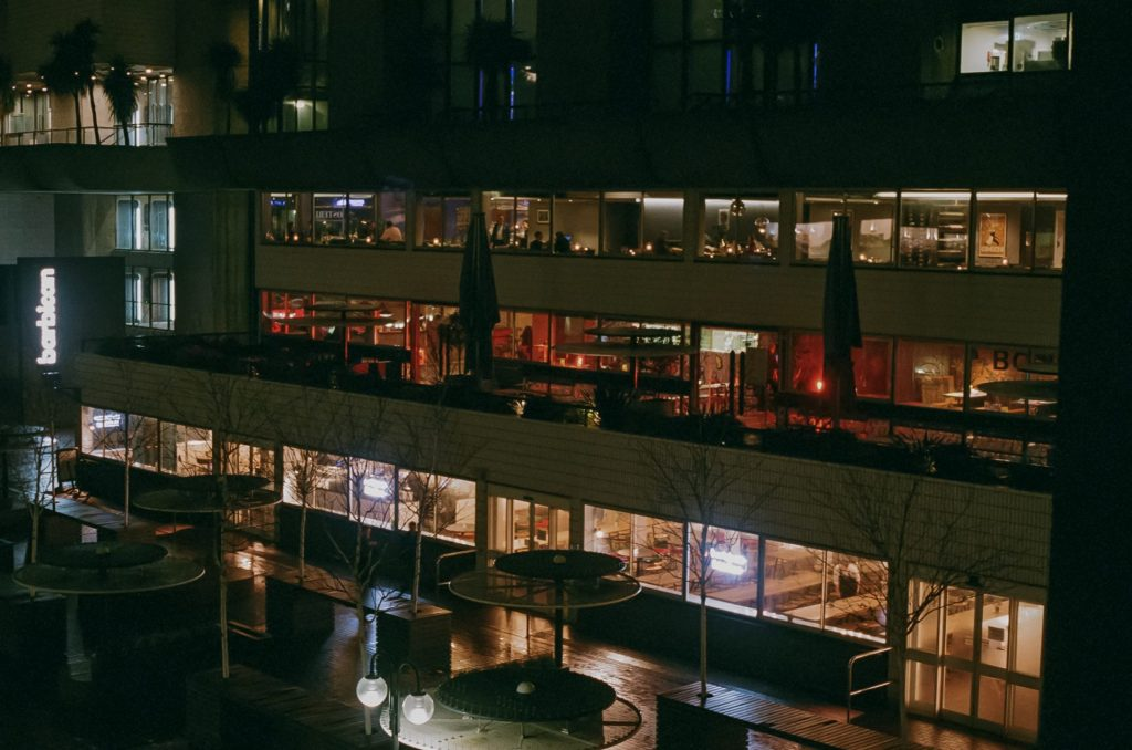 A night time view of a a multi-floor building with from the side angle about halfway up an adjacent building