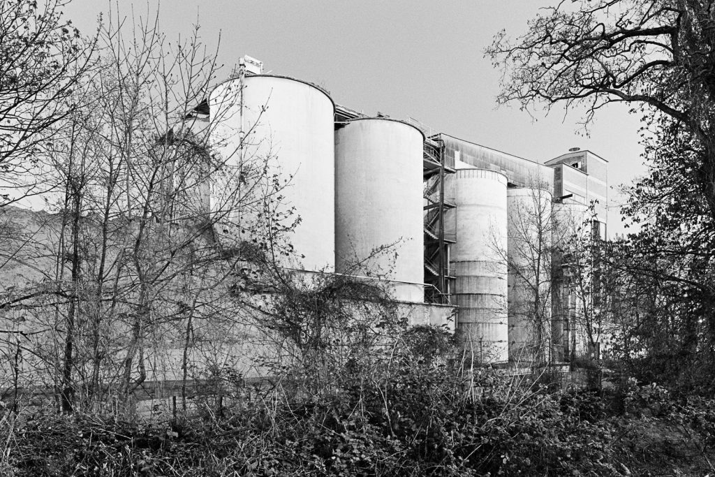 Black-and-white photographs of cement silos at the site of an abandoned factory.