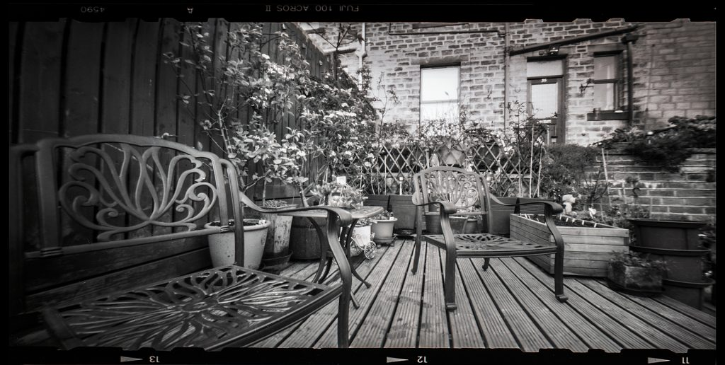 Low viewpoint of a decked back yard in black and white