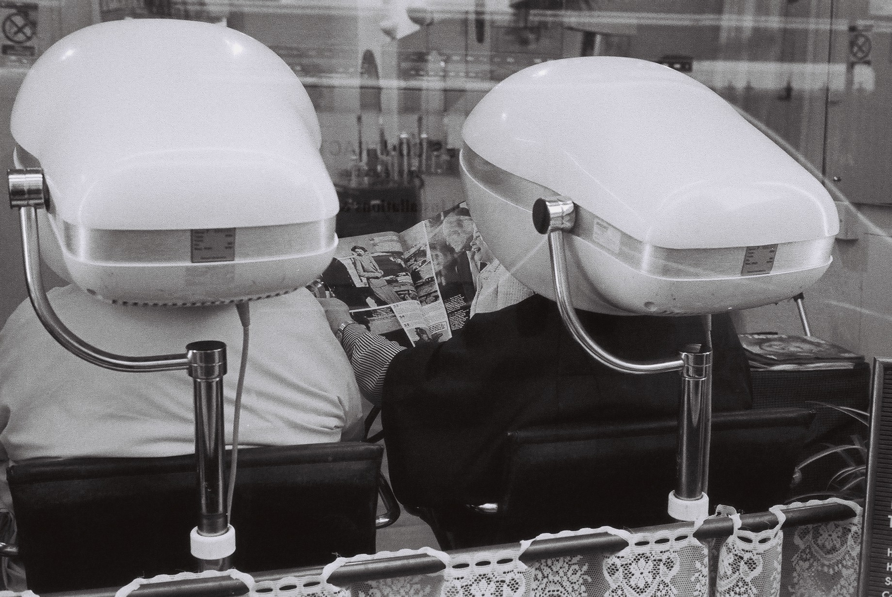 Two women in hairdresser under hairdryers