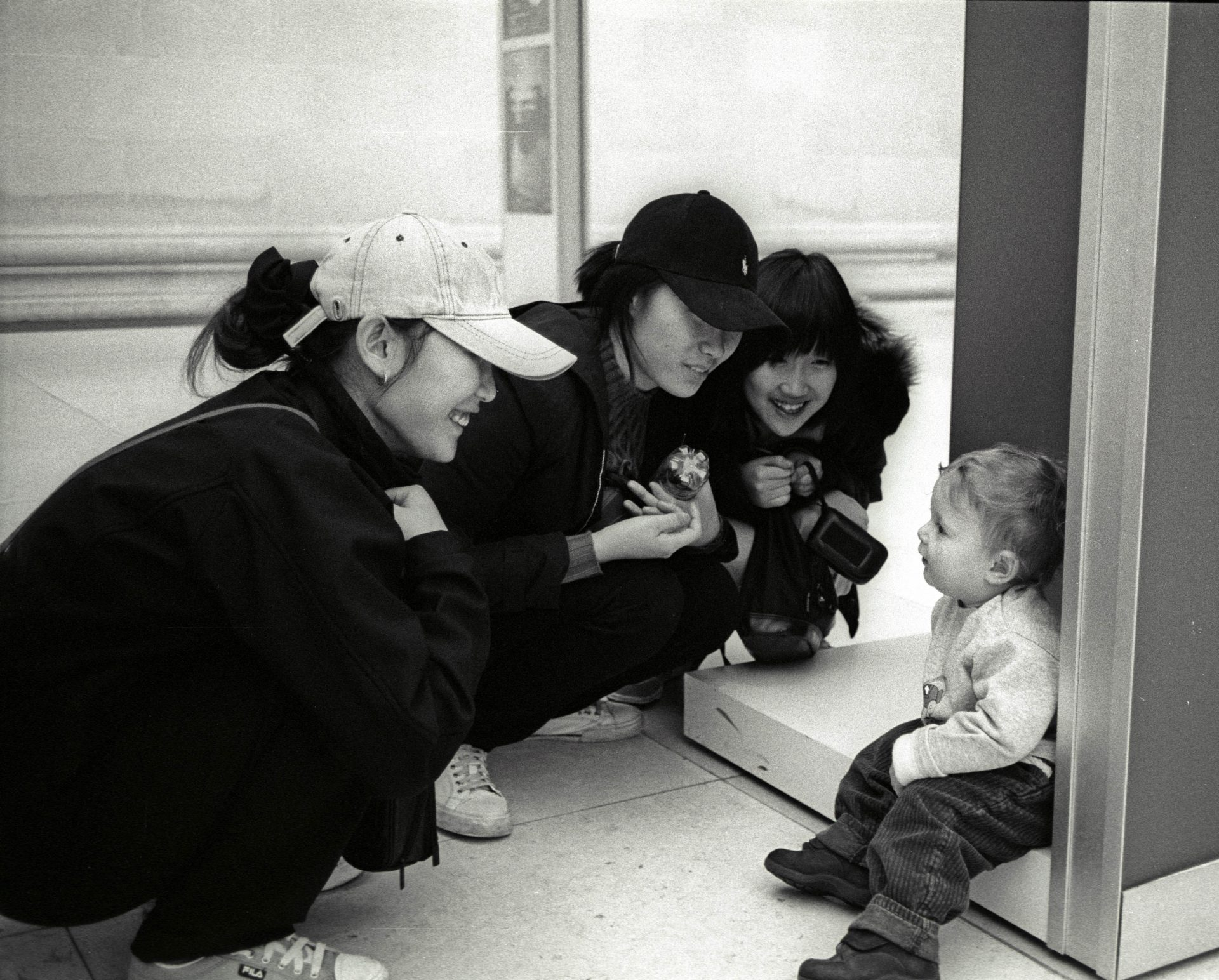 women crouching down looking at toddler