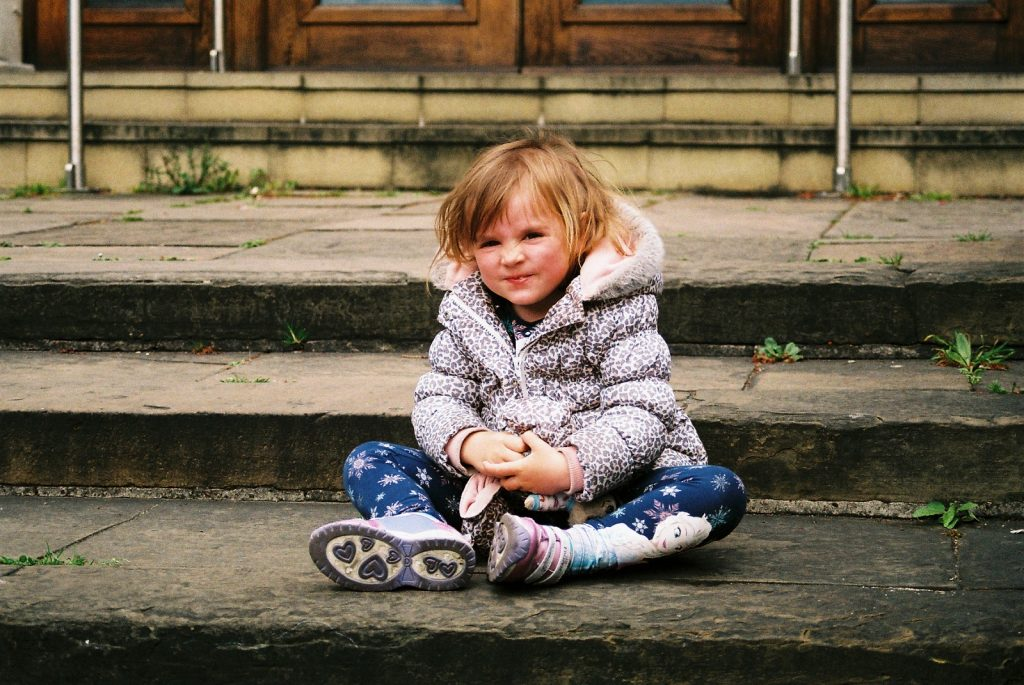 photo of young child sitting on steps