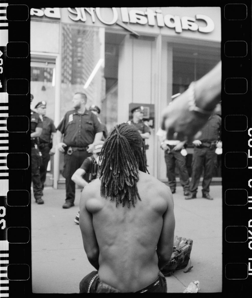 Guy kneeling before the police