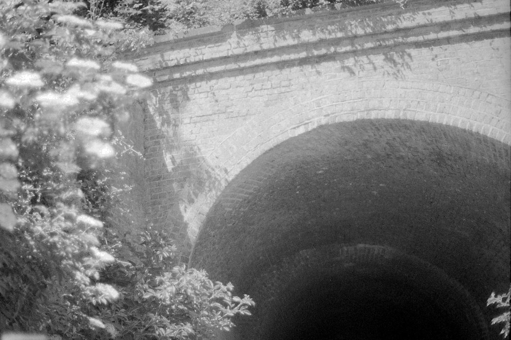 black and white photo of tunnel under railway