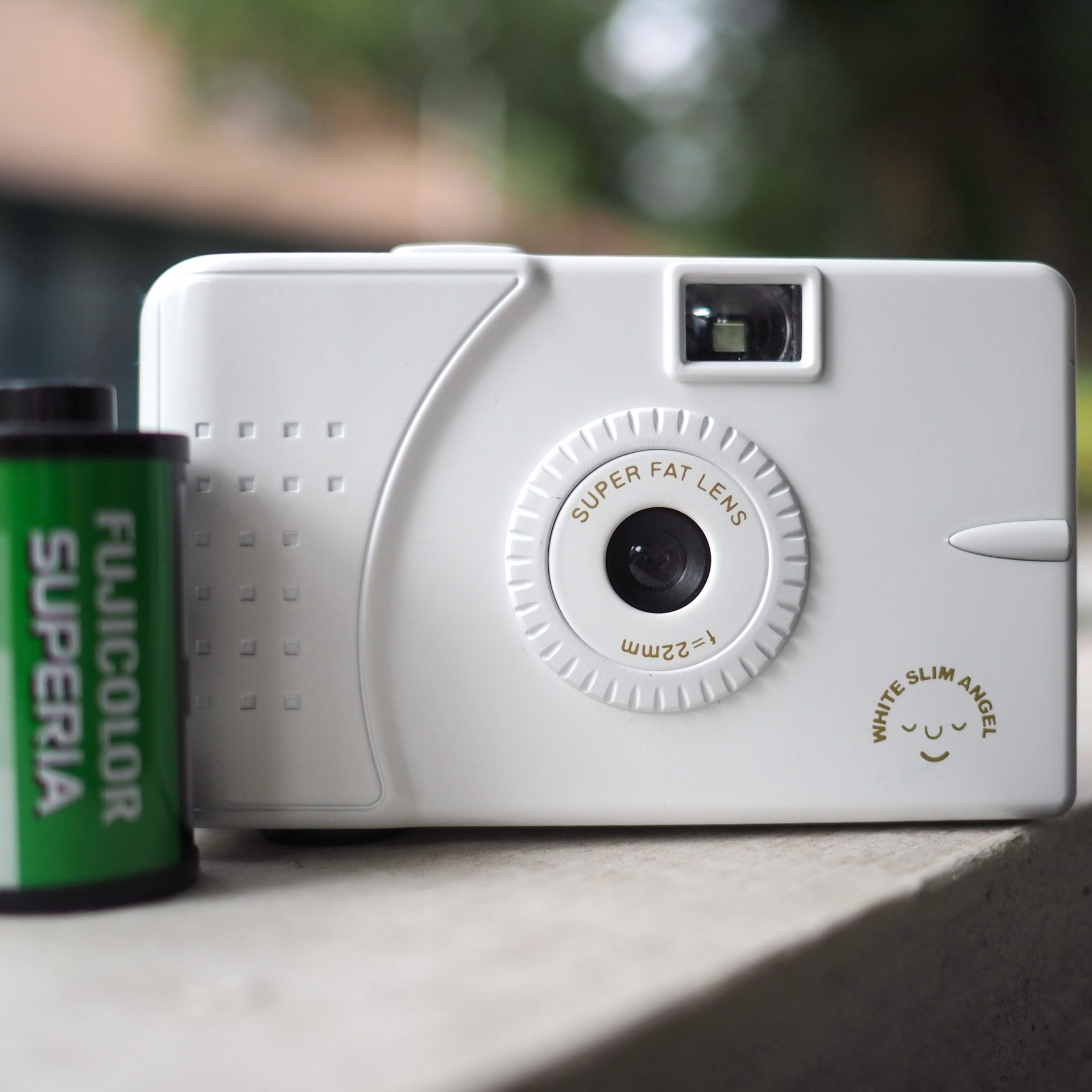 White Slim Angel 35mm film point and shoot plastic camera with roll of Fuji film