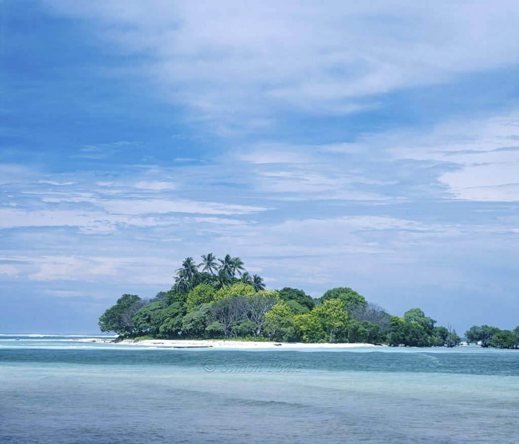 Tropical island, shallow sea bed and light clouds.