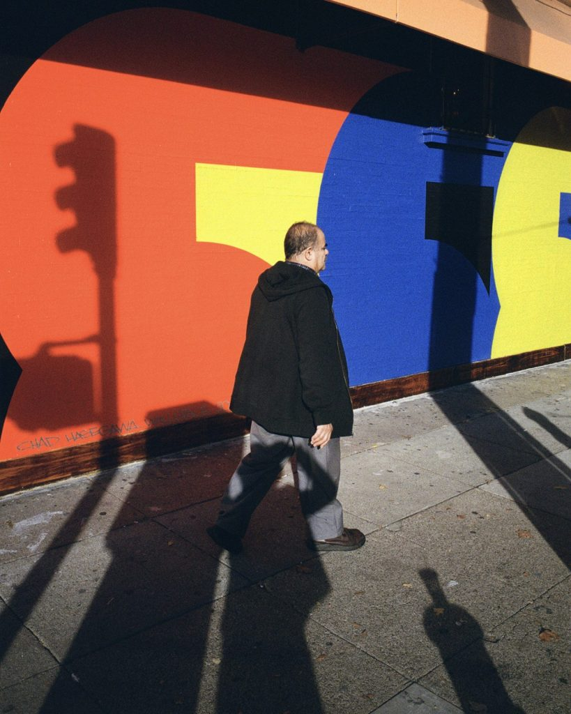 A man walking by a painted mural