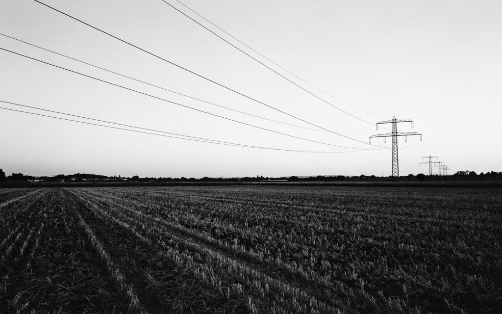 Agricultural landscape close to the village Ingeln-Oesselse in northern Germany: power poles standing on harvested fields