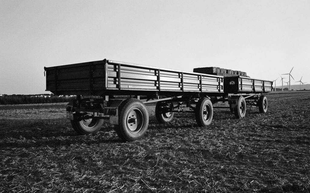 two farming trailers parked on a field