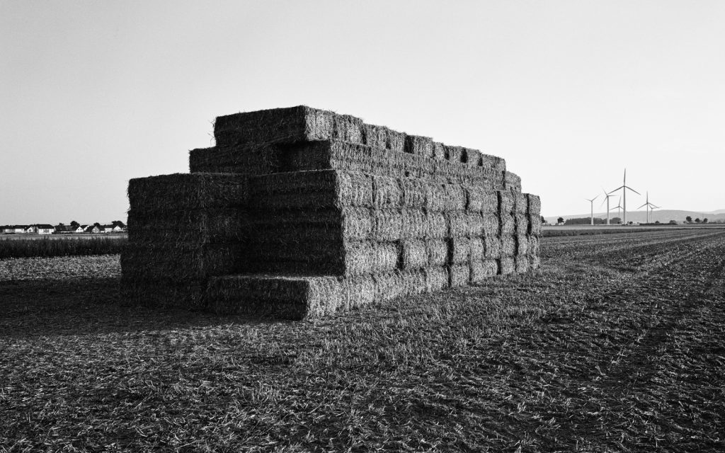 agricultural landscape with a stack of boxy straw bales