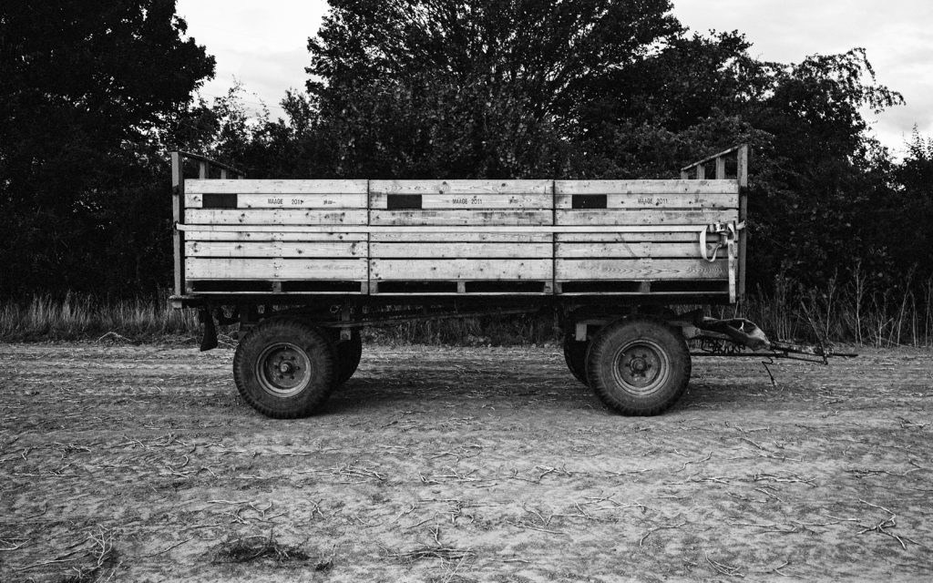 empty farming trailer parked at the side of a potato field
