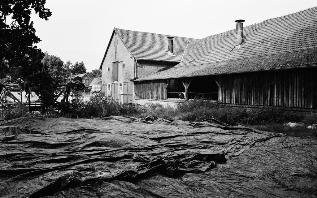 farm house with tarps spread out in the foreground