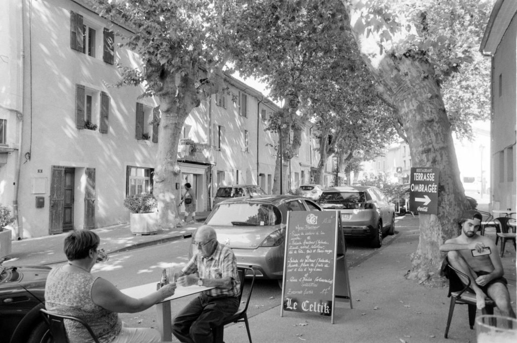 People sitting outside a French village bar