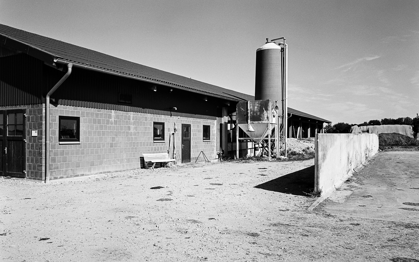 A modern cow barn with a silo tower on its side.