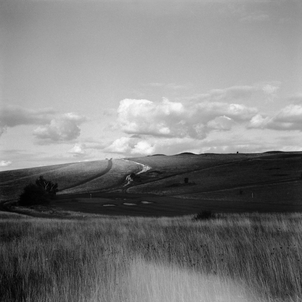 Grassland and a hill with a prominent light leak in the bottom of the frame