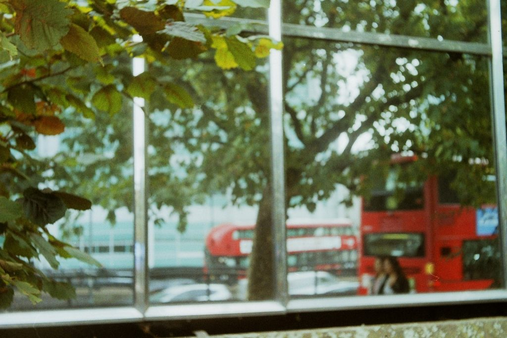 photo of a red bus reflected in a window