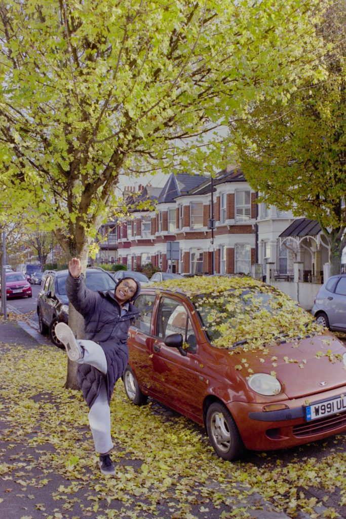 Autumn tree and car. Girl kicks the fallen leaves