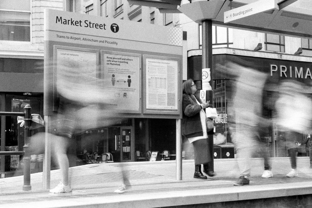 Blurred people walk past a lady waiting for a tram and a social distancing poster