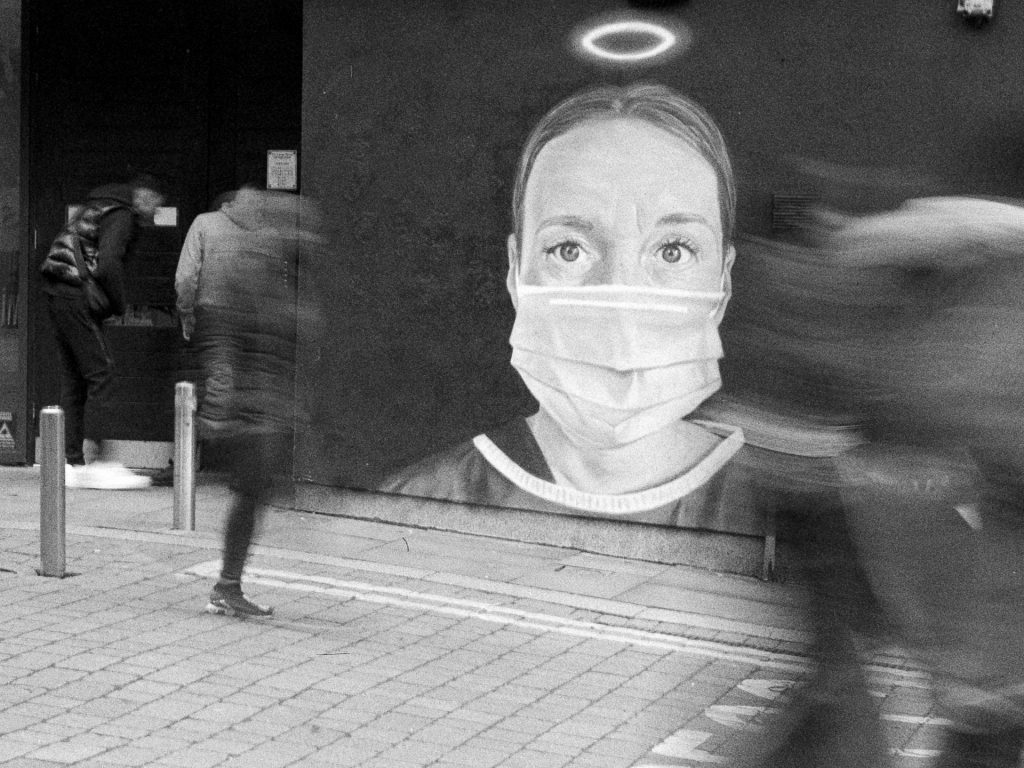 Blurred people walk past street art showing a masked nurse with a halo over her head