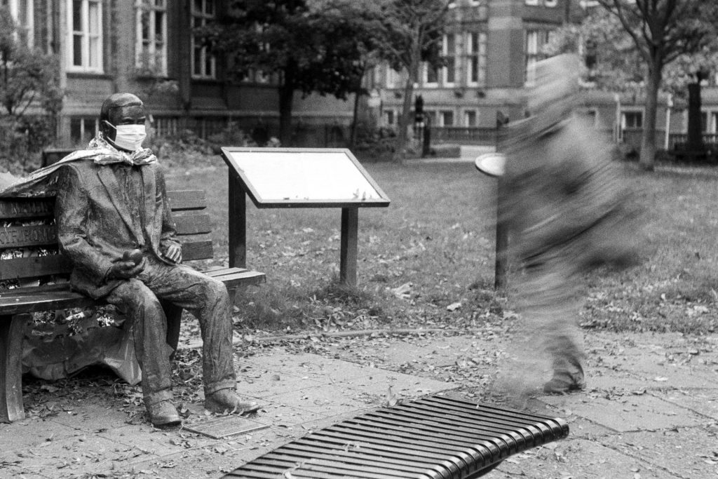A blurred person walks past a seated statue of Alan Turing that has had a mask put on it