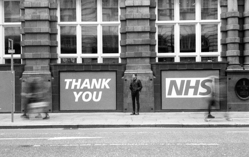 A man standing between large signs thanking the NHS while blurred people walk by