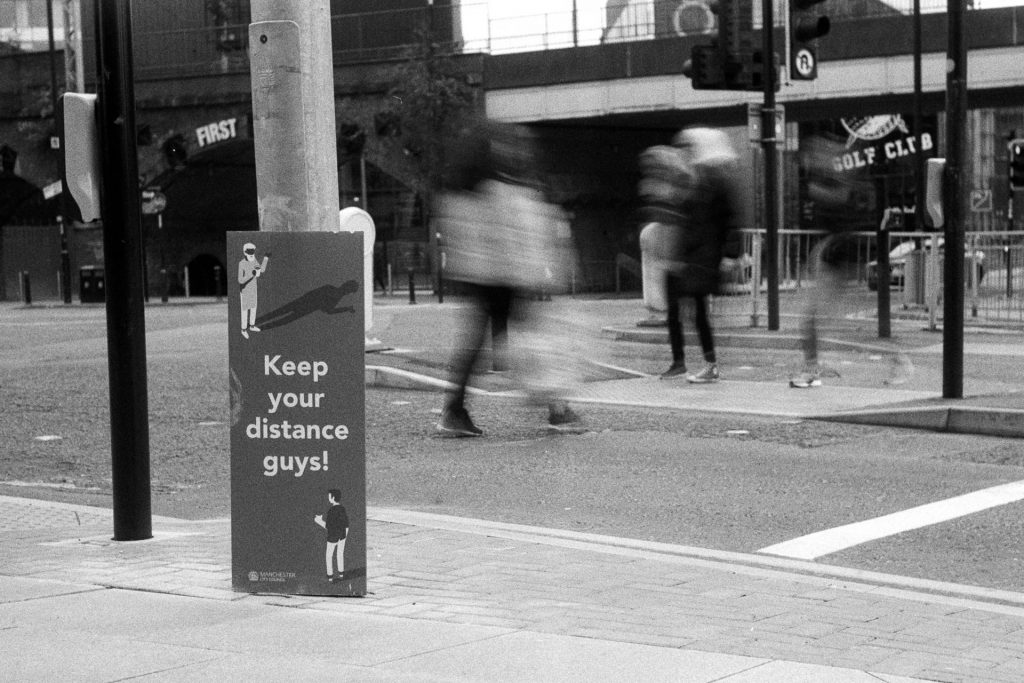 A sign saying 'Keep your distance guys' at traffic lights with blurred people crossing the road