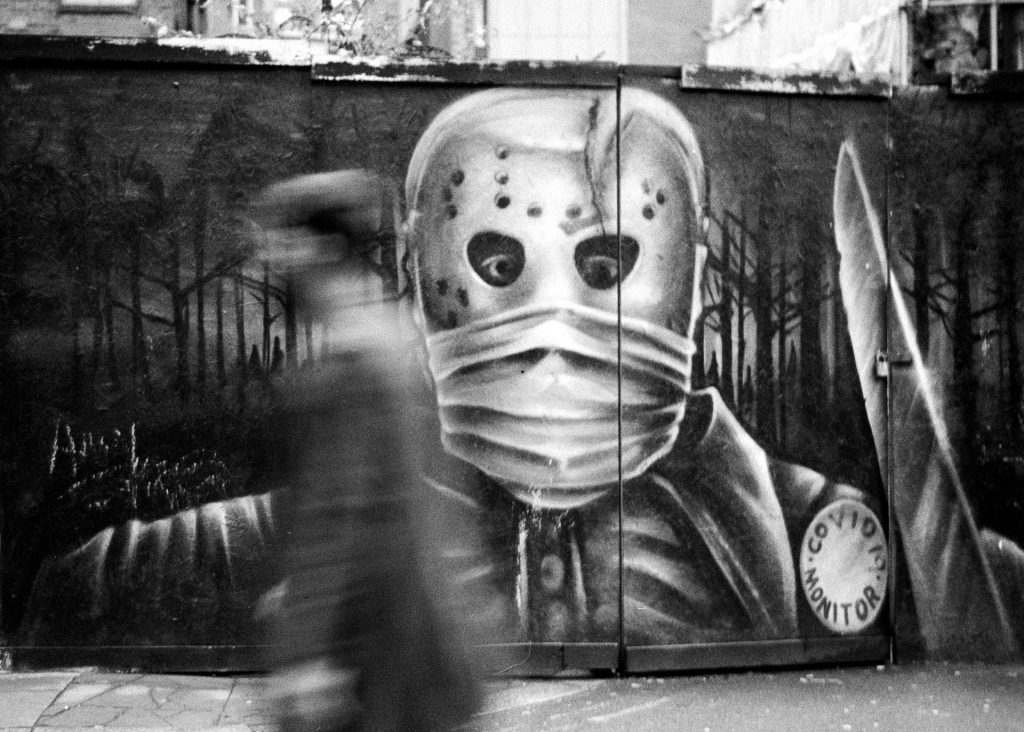 A blurred person walks past street art of a scary knife wielding Covid-19 monitor