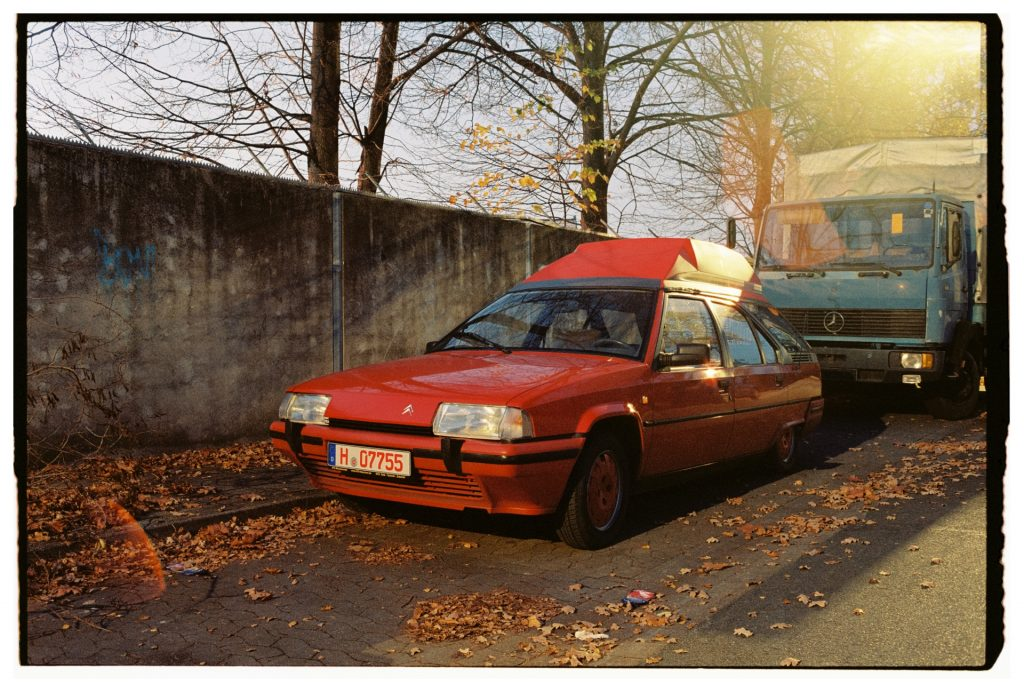 a red Citroen car parked at the side of a road, in front of a dark concrete wall