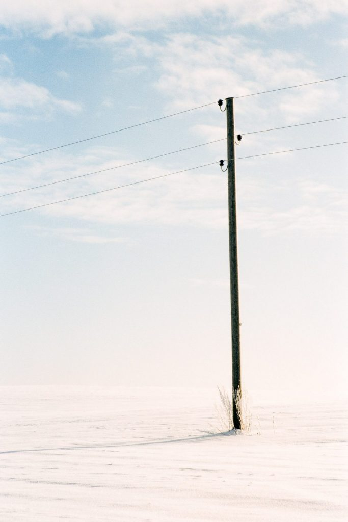 Photo of a single electricity pole in winter shot on slide film.
